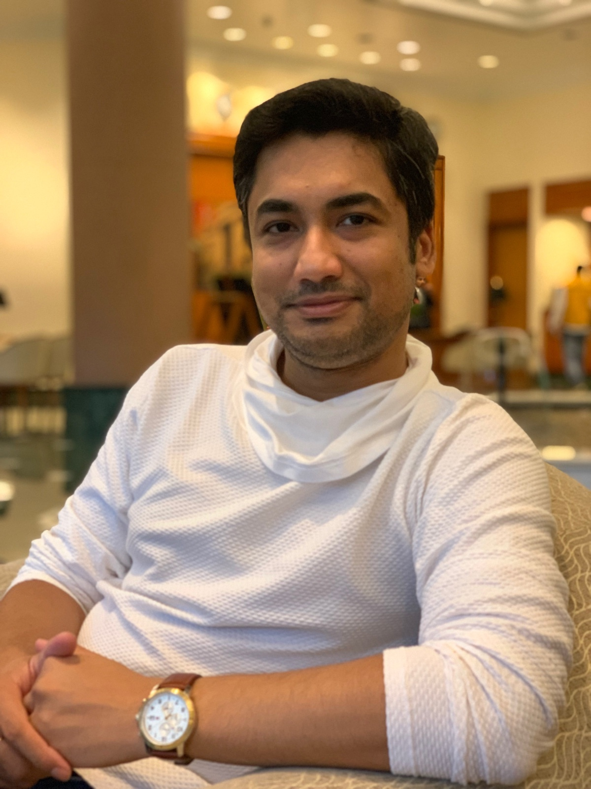 Abhijeet Mukherjee smiling in a white high neck